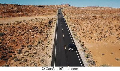 Drone following silver car on empty desert highway road in...