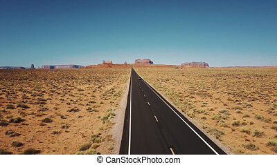 Drone follows car moving along iconic American desert...