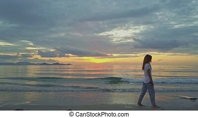 Drone Follows Girl Going along Beach against Sea Sunrise