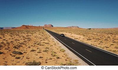 Drone follows silver car driving along amazing American...