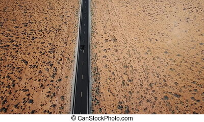 Drone follows silver car driving along dry American desert...