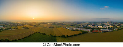 Drone footage - sunrise view over fields and a nearby situated business district, covered by the fog of the early wet morning.