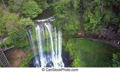 drone goes down to waterfall among lush jungle - drone goes...