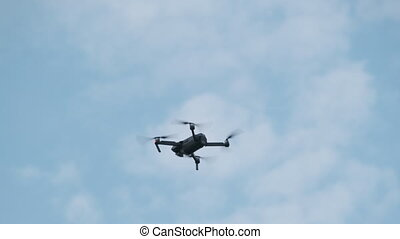 Drone Hangs in the Air against the Blue Sky, view from below. The quadcopter with a camera hovers at a low altitude. Fast rotating drone propellers. Slow Motion