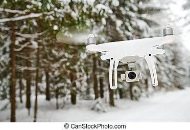 drone hovering in winter forest
