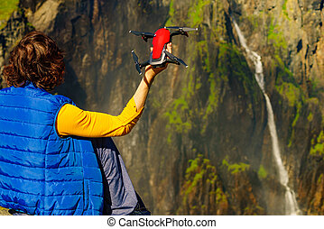 Drone in female hand against nature