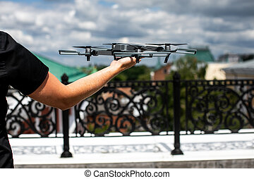 Drone landing on hand. Drone and photographer man hands. drone copter flying with digital camera