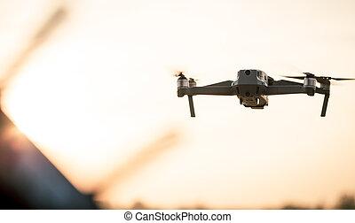 Drone like Mavic 2 Pro flying during sunset.