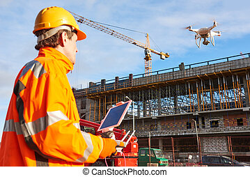 Drone operated by construction worker on building site -...