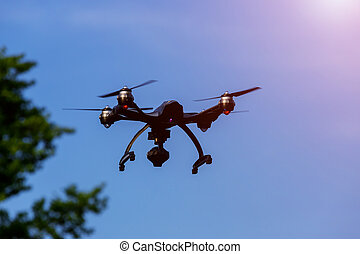 Drone or UAV flying overhead in blue sky