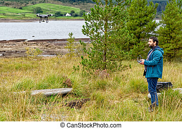Drone pilot after take off with a DJI drone in Galloway Forest Park, Scotland - united Kingdom - 15th of September 2020