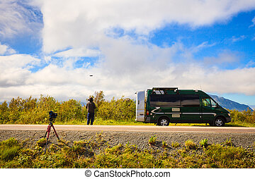 Camper van in summer norwegian landscape and drone pilot or stock photographer flying high technology drone. Lofoten archipelago Norway. Tourism vacation and travel. Explore nature