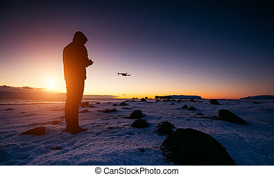 Drone pilot with unmanned aircraft in beautiful sunset ligt