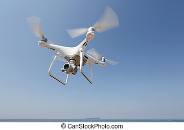 Drone quad copter with flying in the clear blue sky