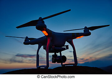 drone quadrocopter with digital camera at sunset - drone...