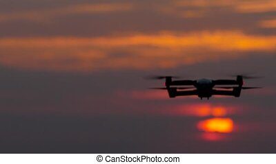 Drone revolves around its axis against the background of the sunset