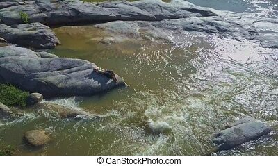 Drone Rotates around Girl Lying on Boulder among Stormy...