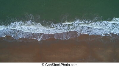 drone shot of a beach with waves rolling