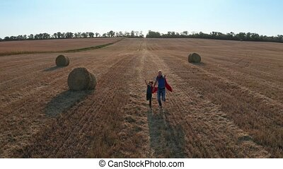 Drone shot of father and son running across field