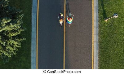 Drone shot of gay couple biking along bicycle path -...