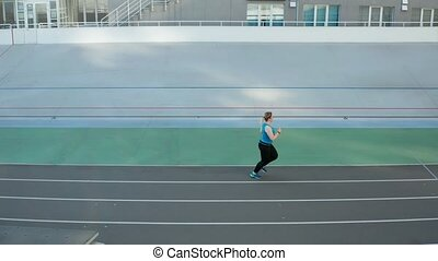 Drone shot of overweight runner during training - Aerial...