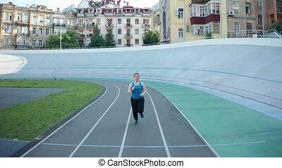 Drone shot of plus size female jogging at stadium - Back...