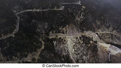 Drone shot two winding roads, a dam and a reservoir in wooded mountains