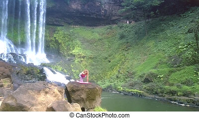 drone shows girl on high rock against waterfall