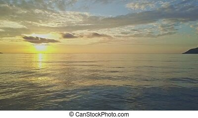 drone flies and shows excellent morning seascape merging with pictorial golden sunrise on horizon