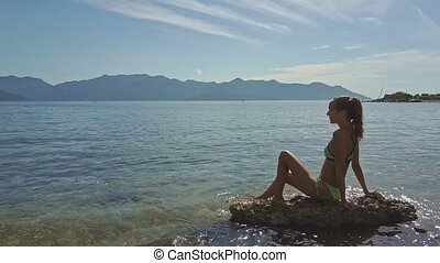 Drone Side View Girl Sits on Stone in Shallow Sea with Gleams