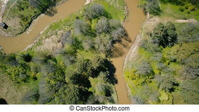 Drone spinning close over winding dirty river. Aerial 4K...