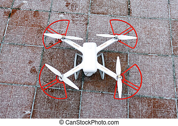 Drone stands in the snow on a red-brown tile. ready to fly in winter