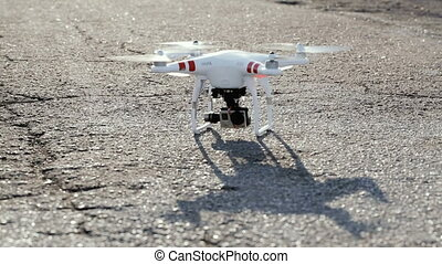 Drone stands on asphalt and takes off into the sky - Drone...
