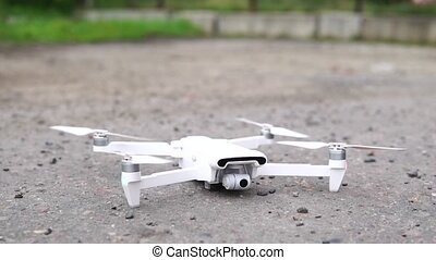 Quadcopter takes off on the street, close-up.