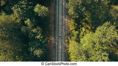 Drone top view of man running on train track. Escaping from past problems. Chasing dreams and surviving life trials.