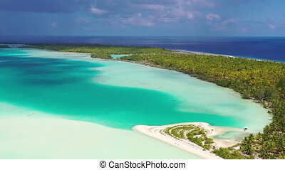 Drone video of French Polynesia Tahiti Fakarava atoll and famous Blue Lagoon and motu island with perfect beach, coral reef and Pacific Ocean. Aerial Tropical travel paradise in Tuamotus Islands.