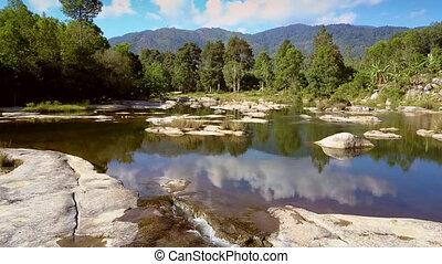 green river streams on rocks against tropical landscape