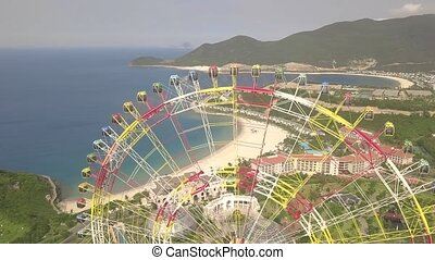 Drone view colorful ferris wheel in amusement park on sea and mountain landscape. Amusement park with large ferris wheel on green highlands background. Aerial view.