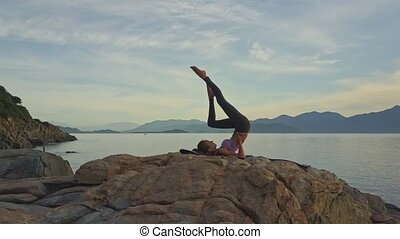Drone View Girl Bends Knee in Yoga Pose against Green Hills...