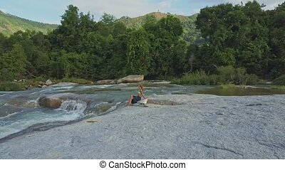 Drone View Girl Sits on Stone against Hilly Landscape -...