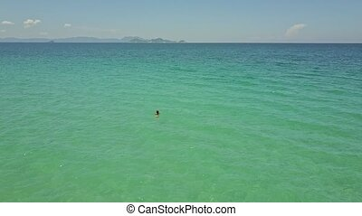 Drone View Girl Swims in Ocean against Distant Hills on Skyline