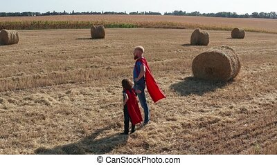 Drone view of dad with son superheroe poses