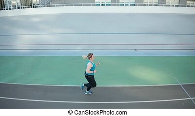 Drone view of overweight woman running along track - Aerial...