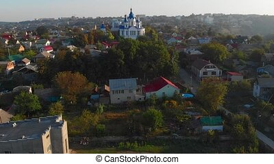 Slow aerial approach over treetops of Saint George Orthodox Church, a prominent landmark in Kamianets Podilskyi, Ukraine.