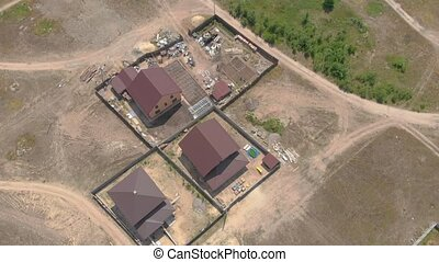 Drone view private houses forest village aerial bird eye backward push out tilt up camera movement