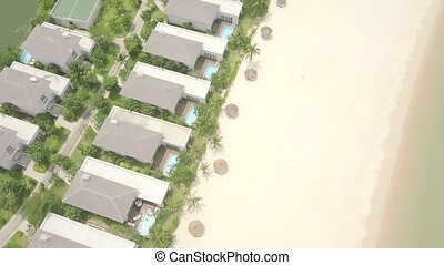 Drone view tourist resort villa and mansion with swimming pool on sea beach. Luxury cottage village with swimming pool on shore blue sea. Aerial landscape architecture tourist hotel on ocean coast.