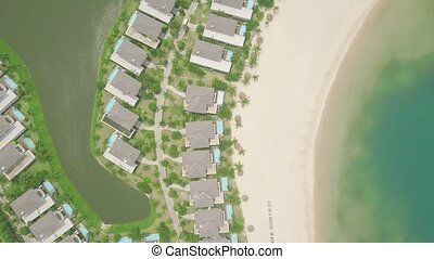 Drone view tourist resort villa on sea shore. Luxury cottage village with mansion and swimming pool on shore blue sea. Aerial landscape architecture tourist hotel on ocean coast.