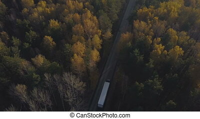 Drone view truck car moving on highway road through autumn forest