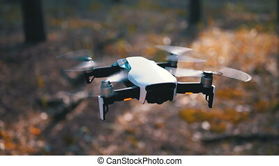 Drone with a Camera Hovers in the Air above the ground in ...