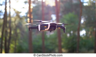 Drone with a Camera Hovers in the Air. Flies above the ...
